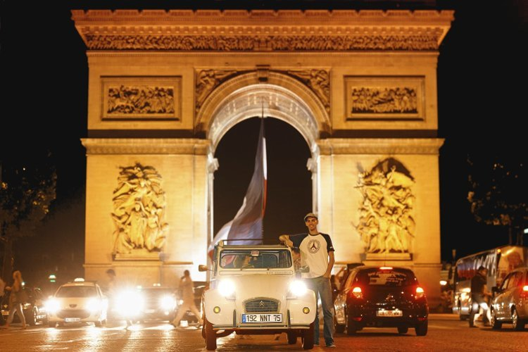 Citroën 2CV cocorico facing the Champs Elysees at night