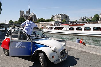 Citroën 2 CV am Seine Ufer mit einem Bateau Mouche