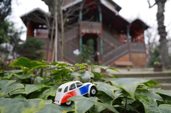 Citroën 2 CV Miniatur vor einem Strauch