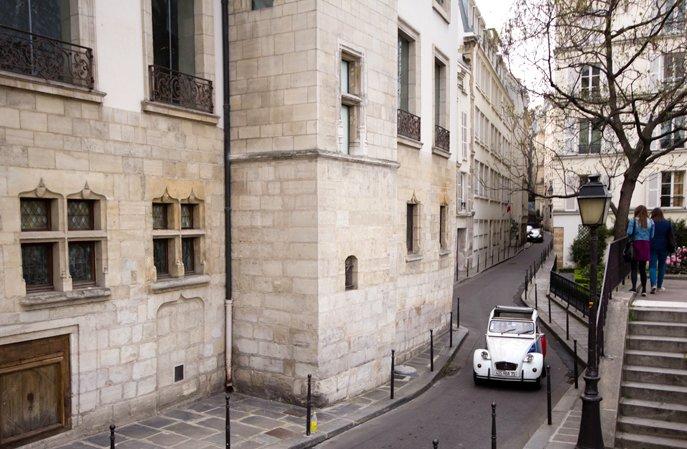 2CV con conductor que camina por París